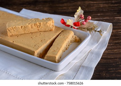 Spanish almond nougat in white plate on wooden table. Soft Turron the Jijona, traditional Christmas dessert in Spain. Christmas sweet background.