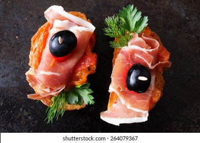 Spanish appetizer with jamon on a black background top view