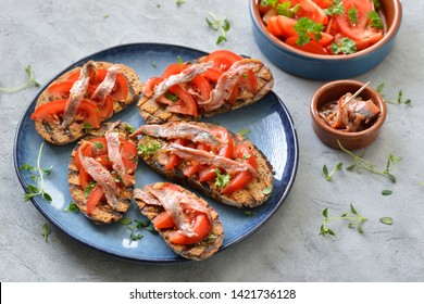 Spanish bar food: Grilled slices of bread with olive oil, herbs, fresh tomatoes and spicy anchovy fillets