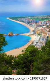 Spanish beach resort Blanes in summertime. Coast, rock Sa Palomera and architecture. Sunny panorama from height of mountain of castle San Juan. Costa Brava, Catalonia, Spain