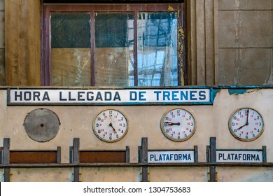 """Spanish cartel with """"time to train arrival"""" text and analog clocks at abandoned old train station platform in aguada district, Montevideo, Uruguay"""