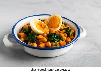 Spanish chickpea and spinach stew with eggs on light gray background with copy space. Spanish cuisine. Traditional Spanish recipe prepared in Holly Week and Lent. Vegan Potaje de vigilia. Horizontal.