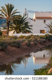A Spanish church reflected in a small stream