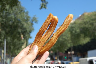 Spanish Churros being held up