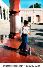 Spanish Colonial city of Alamos, Mexico, Young woman sweeping sidewalk, December 1, 2000