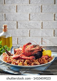 Spanish Fideua, a noodle Paella with prawns, fish, calamari, mussels served on a white plate on a grey rustic wooden table with a brick wall at the background, vertical view from above