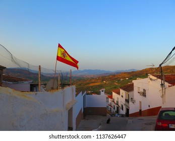 Spanish flag blowing in the wind from house overlooking Valley in Andalusia, Spain