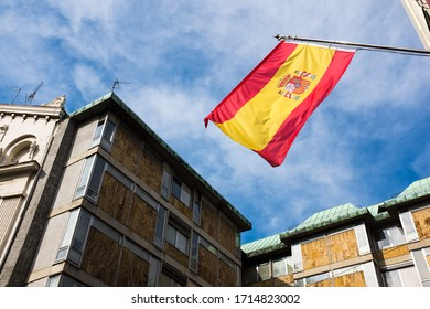 Spanish flag flapping on the wind, against blue sky,attached to building facade,hope and faith after surviving Coronavirus COVID-19 pandemic crisis,positive feelings and recovery of fallen economy