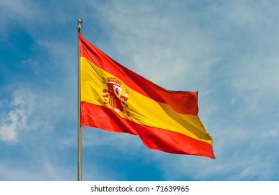 spanish flag on a pole over beautiful sky