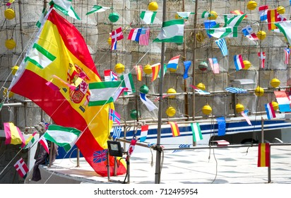 Spanish flag and other international flags on a fishing boat. Carboneras. Spain.