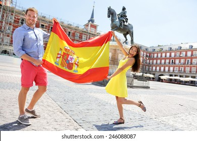 Spanish flag. People showing Spain flag in Madrid on Plaza Mayor. Happy cheering celebrating young woman and man holding and showing flags to camera on the famous square.