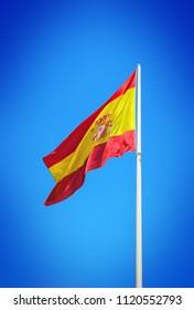 Spanish flag waving against clear blue sky