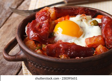 Spanish Food: Baked eggs with chorizo and vegetables in the pot. close up horizontal
