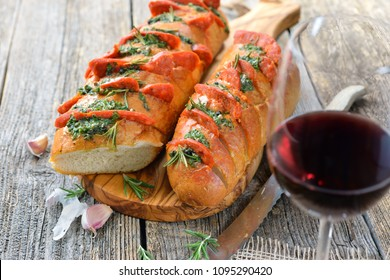 Spanish food: Roasted bread with herb butter and hot Chorizo salami fresh from the oven served with a glass of tempranillo red wine