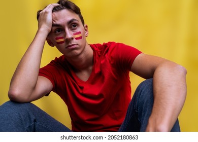 Spanish football fan sad for his national team, isolated on yellow background. Flag painted over face