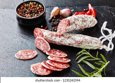 spanish fuet sausages cut in slices on a black slate plate with peppercorns, sliced chili and fresh rosemary, view from above, close-up