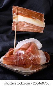 """Spanish ham, called """"Iberico"""", with a flag done with a slice, on black background."""