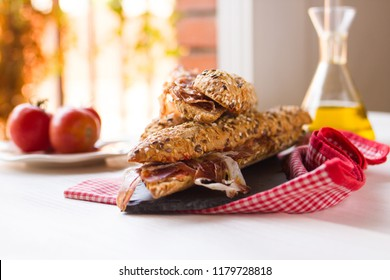 Spanish ham sandwich close-up with olive oil, tomato and garlic. Traditional catalan cuisine appetizer known as bocadillo de jamón, made with iberian ham.