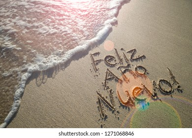 Spanish Happy New Year message (Feliz Año Nuevo) handwritten with textured lettering on smooth sand beach with lens flare above oncoming wave
