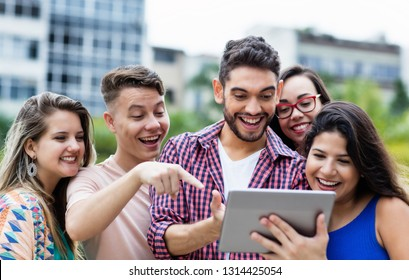 Spanish hipster student with tablet computer and group of cheering international students outdoors in summer in the city