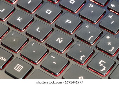 Spanish keyboard laptop focused in the characteristic letter Ñ of the Spanish alphabet and with illuminated keys