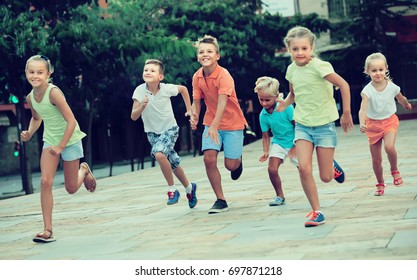 spanish  kids actively playing and running together on street on summer day