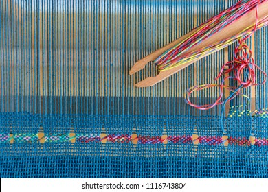 Spanish lace weaving on rigid heddle loom with blue warp and colorful weft