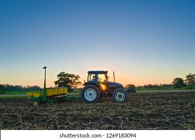 Spanish lookout, Belize - December 8, 2018 Garren Koop planting corn in Spanish lookout with a New Holland Tractor while the sun is setting