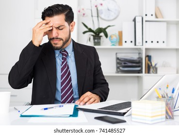 Spanish male worker is having complicated issue with project in office.