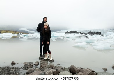 Spanish man and Asian girl pose on top of some rocks near the Jokulserlon glacier in Vatnajokull National Park, Iceland, where misty mountains can be seen on the background.