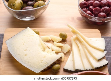 Spanish manchego cheese on wooden board with olives