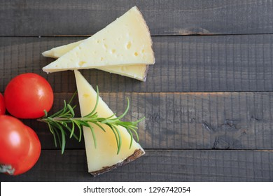 Spanish manchego cheese sliced on a wooden background with a sprig of rosemary and tomatoes. View from above