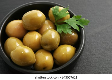 """Spanish olives in """"tapa"""" served with parsley."""