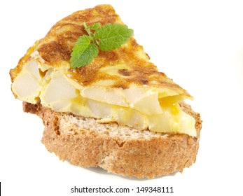 Spanish omelet on bread slice with mint leaf garnish isolated on white background closeup, typical appetizer