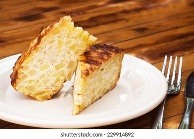 Spanish omelet on a white plate. The plate on the wooden table. Spanish omelette with potatoes and onion. Tortilla espanola (wooden table background).