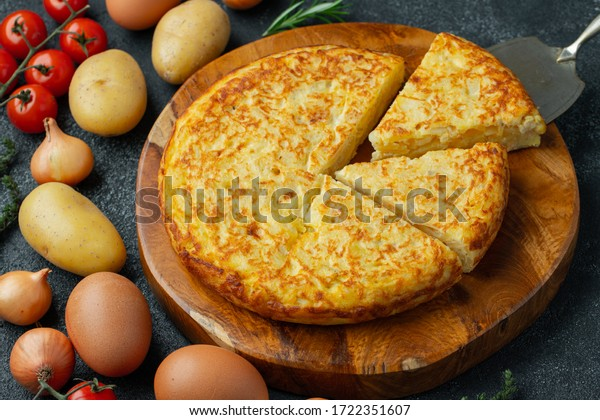 Spanish omelette with potatoes and onion, typical Spanish cuisine. Tortilla espanola. Rustic dark background. Top view