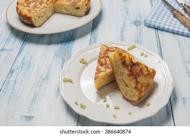 Spanish omelette with potatoes and onions presented its ingredients on white table and blue