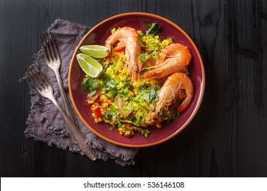 Spanish paella with seafood on the red teralke with lime. Delicious lunch on the shore of the sea shrimp. Dark wood background