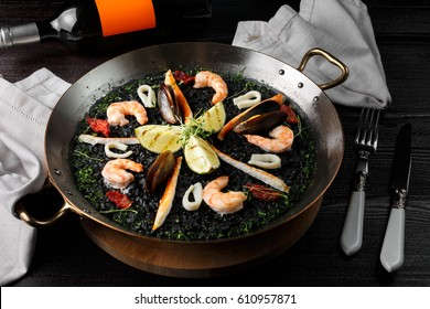 Spanish paella with shrimps. The black paella is Spanish. Classical Spanish cuisine. Shrimp, lime, wine.