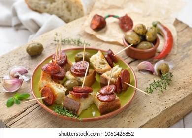 Spanish pinchos: Fried spicy chorizo sausage on roasted bread
