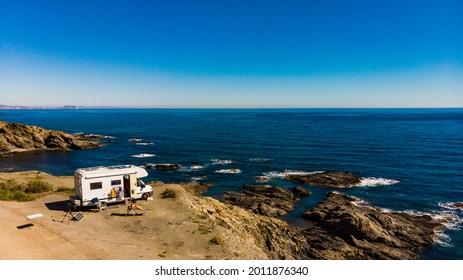 Spanish rocky coastline with camper car camping on cliff sea shore. Mediterranean region of Villaricos, Almeria, eastern Andalusia, Spain.