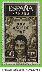 """SPANISH SAHARA - CIRCA 1965 : A stamp printed in Spain with Illustration of a Sahrawi woman smiling and the message """"25 years of peace"""""""