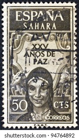 """SPANISH SAHARA - CIRCA 1965: A stamp printed in Spain shows a woman in traditional outfit and and the inscription """"25 years of peace"""", circa 1965."""