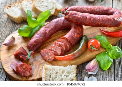 Spanish salami: Spicy chorizo sausage with tomatoes and basil served on an olive wood cutting board
