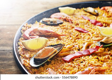 Spanish seafood paella in traditional pan on wooden planks.