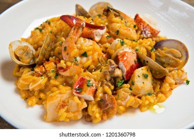 Spanish Seafood Risotto served on a white plate with mussels, shrimp, squid and crab