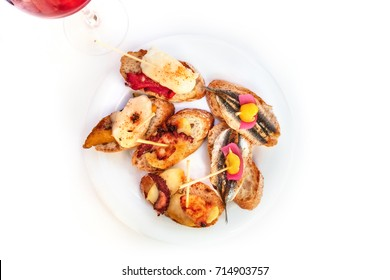 Spanish seafood tapas, with pulpo, fish, and a glass of wine, on a white background, overhead shot