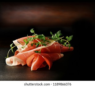 Spanish Serrano ham with fresh thyme herb garnish shot in a dark, creatively lit setting with generous accommodation for copy space.