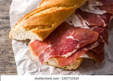 Spanish serrano ham sandwich on wooden table. Close up