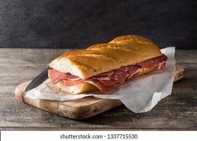 Spanish serrano ham sandwich on wooden table.